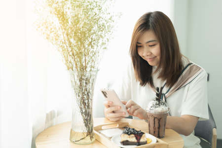 Woman is checking Bitcoin price chart on digital exchange on smartphone in the cafe
