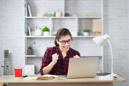 Beautiful asian woman talking on cellphone consulting client or customer online and using laptop computer while sitting on table.