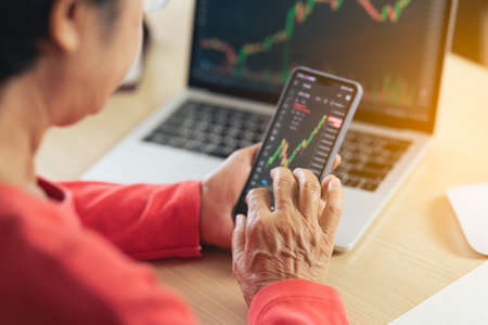 Senior woman depression and serious about checking Bitcoin price chart on digital exchange on laptop