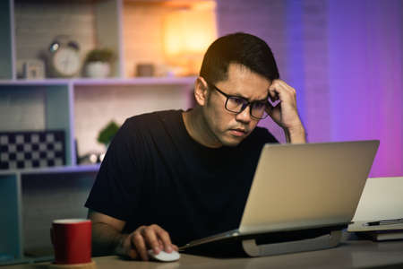 freelancer man serious and busy working with laptop on the table, work from home concept
