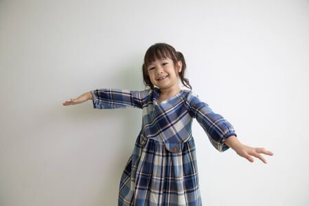 half-body and front-view photo of adorable, three-year-old Asian girl posing on a white background shows her brightness that makes people look happy, bright and cute.