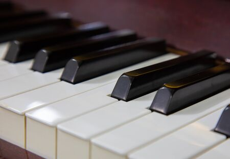 Close-up or macro image of piano keys by selective focus technique can be seen the details of classic instruments used in both Jazz and pop music which background and foreground are blurred.
