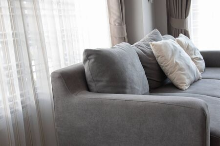 Close-up picture of grey soft with side pillows are comfortable, yet stylish and modern, for the whole family to spend their free time resting under the evening light that has escaped through the window. Standard-Bild