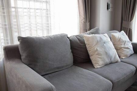 Close-up picture of grey soft with side pillows are comfortable, yet stylish and modern, for the whole family to spend their free time resting under the evening light that has escaped through the window.