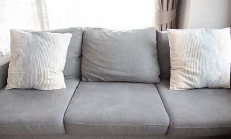 Close-up and front view picture of grey soft with side pillows are comfortable, yet stylish and modern, for the whole family to spend their free time resting under the evening light that has escaped through the window. Standard-Bild