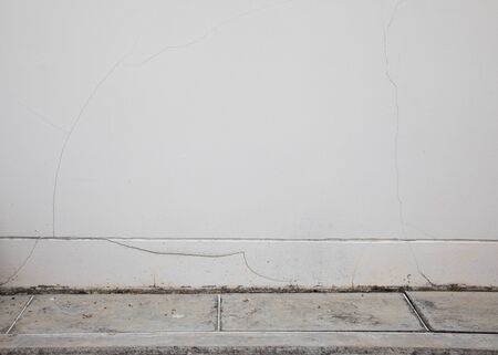 The white walls that have been left outside of the house for a long time show cracks, scratches and water marks. It looks empty and lonely, but beautiful and natural, suitable for making background and backdrop. Archivio Fotografico
