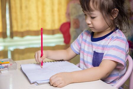 A cute four-year-old Asian girl is sitting and drawing and coloring on her favorite book at home. It develops the skills of preschool children to be ready to study in school and live as they grow up.