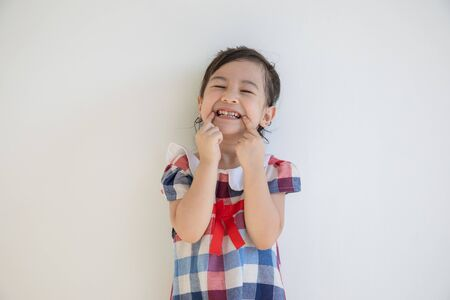 A cute four-year-old asian girl is smiling and acting with the camera. Anyone who sees will feel bright and happy with positive thoughts. Photos in the studio on a white background for half body shot with copy space.