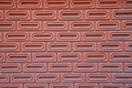 The red brick wall is orange, as background, which is made from the bricks that are ellipsoid inside, arranged horizontally and separated by layers. The wall was built for a long time through the sun through the rain, causing the color to fade over time.
