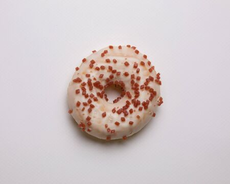 Donuts topped with icing sugar and sprinkled with sugar, pink flakes placed on a white background looks delicious, but be careful not to eat as much as possible because it can cause obesity. Archivio Fotografico