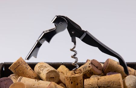 The wine opener was placed with many  corks