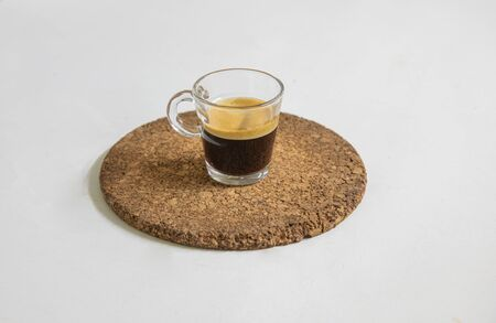 Newly brewed espresso coffee smelling fragrant and frothy places on a corck mat for a fresh, energy-rich starting to the day. Reklamní fotografie - 150124025