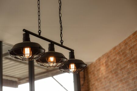 Vintage dome light using filament tungstain gives a warm orange glow in a restaurant decorated with brick walls giving a retro feel.