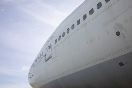 Close-up and high-view shot with beautiful blue sky background of airplane's head part which has been used for flight service for long time showing water stain and rust on the metal surface.