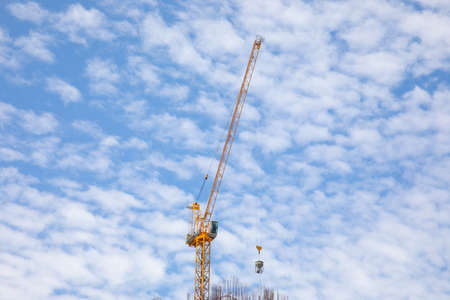 Yellow metal crane is working to construct the building for urban growing business. It seems the Isolate single object on the beautiful blue sky and white clouds as background with copy space.