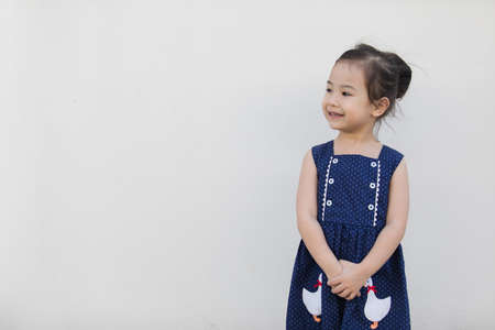 A cute asian girl with a bright blue dress, contrasting with the skin color and white background that everyone will fall in love. Stockfoto