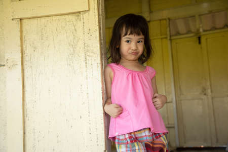 A cute asian girl dressed in folk costume in a country house, standing at the front door of the house, seeing home appliances that reflect rural life.