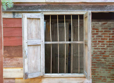 Close up shot of grunge wooden window frame in vintage and retro styles of the rural house which is opening shows beautiful texture of reddish wooden and brick walls with fern tree on the roof.