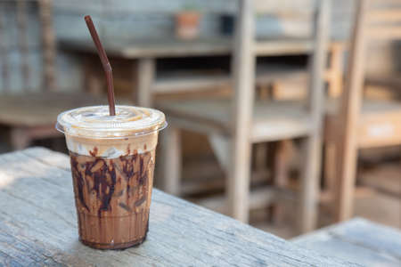 close up shot with blurred background of iced beverage (chocolate, cocoa, mocha coffee) in clear plastic cup put on the vintage wooden table. It looks delicious for drinking cool dessert in summer.