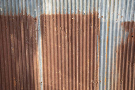 Rusty corrugated metal (tin, aluminium, iron, steel) plates with beautiful color show vertical line texture with fringe and weathered walls which have been exterior outside the old house in city.