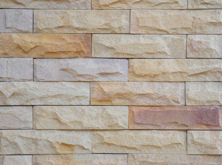 Close up shot of stone bricks with beautiful color (brown, yellow, red, and orange) shows detail texture of grunge, old, vintage and retro style of ancient rock for building house and decoration. Stockfoto