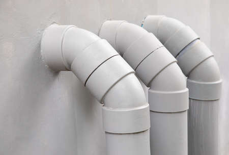 Close Up and selective focus shot of curved and bent PVC plastic tube pipes for water circulation system draining waste from urban house or apartment on white cement wall in vertical direction. Stockfoto