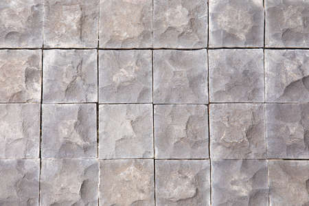 Close up and flat lay shot of vintage granite square rock on pavement ground shows texture and detail of rough surface in square geometry in grid structure. It is beautiful for using as background. Stockfoto
