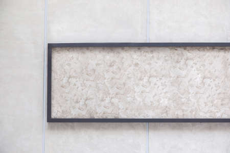 Front view of mock up black window frame with marble texture background and blank is hanging on concrete wall with crack, stain and natural indoor dirty. It is beautiful template for advertisement. Stockfoto