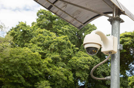 surveillance of cctv camera is installed on the metal pole in the park with yellow taxi reflection on its glass cover to watch and inspect the crime situation for security of the urban people. Stockfoto