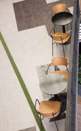Top view of black round table with two wooden chairs with nobody in modern style department store for meeting, dining and relaxing shows concept of social distance and space for business discussion.