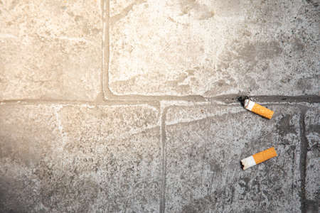 Close up and top view of the finished cigarette butts thrown on concrete floor of the pavement in urban city shows bad habit in environment pollution and risk danger for people health.