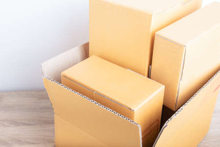 Top view and close up shot of stack boxes in different size from small to large shows beautiful lighting. They are on the wooden desk of online merchandise for selling stuff and delivery to customer.