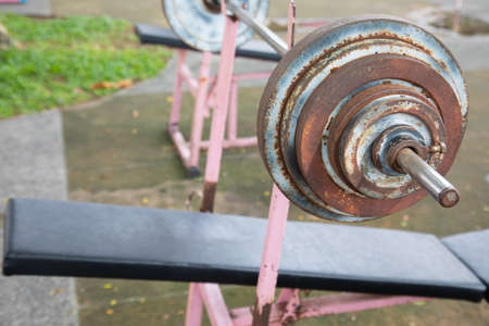 Selective focus and perspective view of old, grunge and rusty barbell equipment in the public outdoor gym which is free of charge for everyone in the community nearby is available for healthy life.