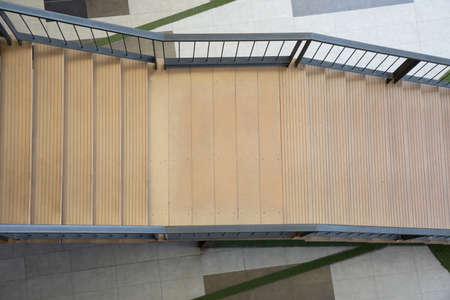 Top view shot of beautiful stairway down from high level to the ground of modern style building with nobody shows the concept of way to success in life or business. It is empty space for frame.