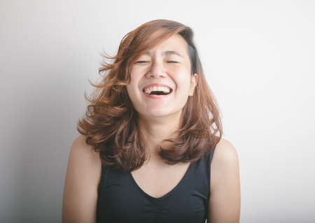 Close up face shot of happily laughing of pretty asian woman model with about 30 years old on black vest shows freshness from her bright eyes, white teeth and tan color skin on white background.