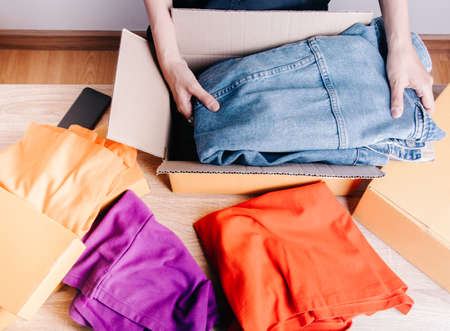 Top view shot of merchandise table with a lot of colorful clothes, jacket jean and boxes for shipping to customers shows modern lifestyle of e-commerce which selling products online through internet. Stockfoto