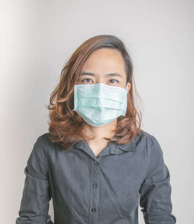 Close up face shot of pretty asian woman model with age of 30s who is wearing medical mask to protect virus and influenza epidemic shows strong and beauty eye contact on white background in studio.