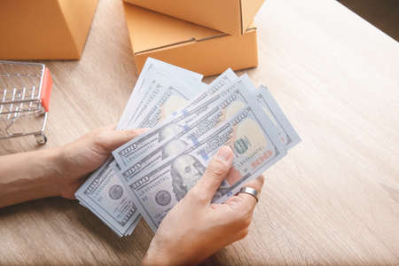 Top view shot of merchandise table with a lot of earning money (mockup banknote) in hands from e-commerce which selling products via online shows boxes and clothes for shipping to customers.