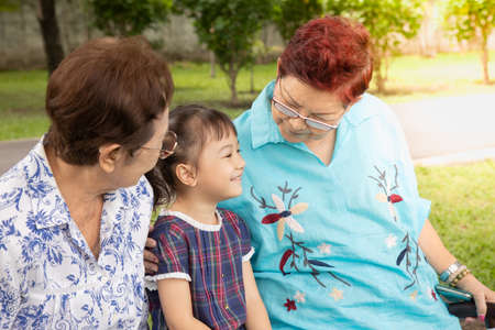 Close up family shot of two grandmothers and their adorable granddaughter posing happily in the park outdoor shows positively smiling faces of senior persons having fun with kidin casual style.