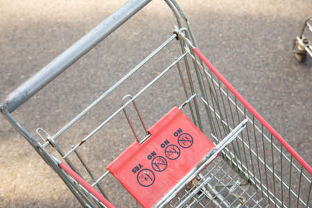 Close up and selective focus shot of empty shopping cart or trolley abandoned outside the shopping mall on the road shows detail of signs, and people habit to left it after delivering all stuffs.