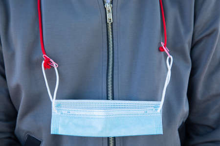 Close up and front shot of white cotton medical mask hung on the neck with strap on the jacket shows the combination of fashion and safety preparation for health, especially in pandemic of flu virus. 免版税图像