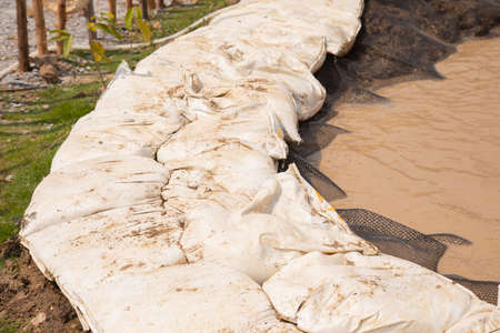 Close up shot of sandbags stacked in row as barrier to protect catastrophe, such as flooding and hurricane, which is caused by environmental problem. The dirty water and mud come to city by raining. Reklamní fotografie