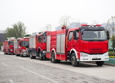 A row of fire trucks parked on the side of the road