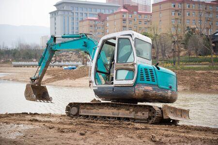 Excavator working on the riverside Stock Photo