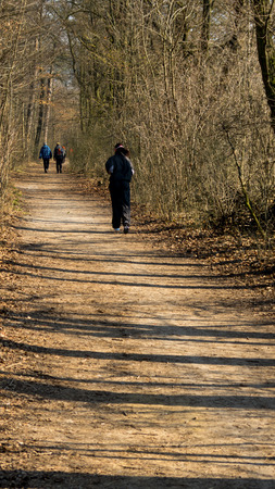 power walking: People sporting on the clay forest path during the first spring day