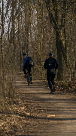 A cyclist pushes runner during the early spring training in the nature