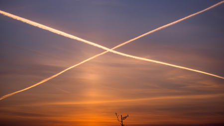 Cross from airplanes' gases on the morning sky Stock Photo