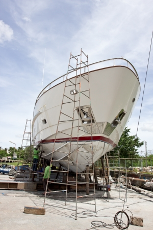 55 years old: Phuket,Thailand, June 11, 2013 Boat repair yard worker inspecting a wooden boat for repair  Editorial