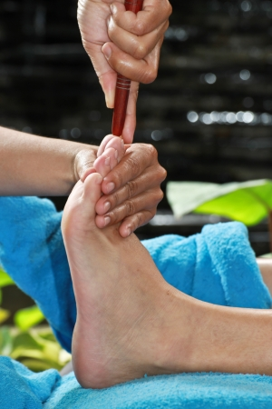 foot massage by wood stick for frontal sinuses  Stock Photo - 23576018