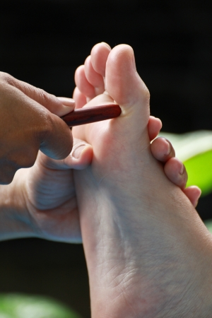 restore energy flow: foot massage by wood stick for neck Stock Photo